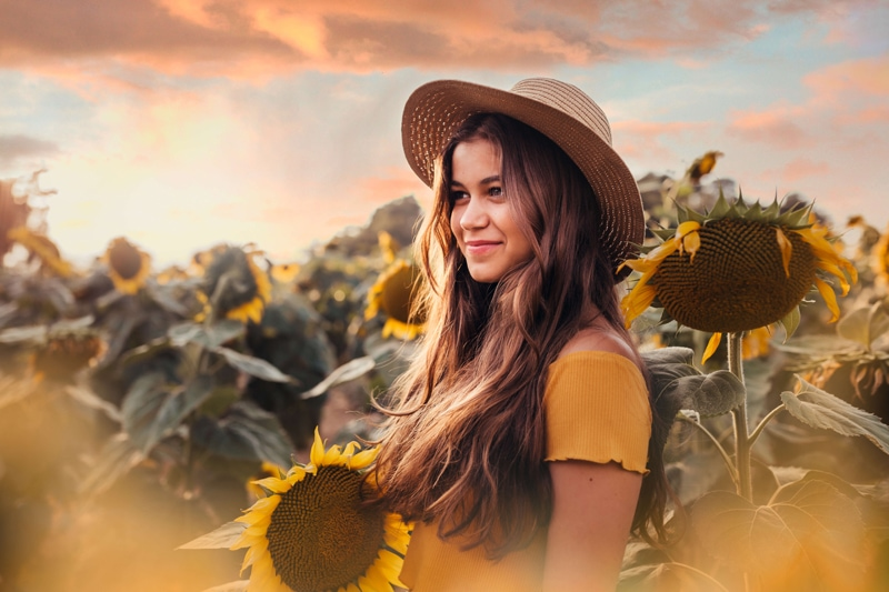 London Family Photographer, a young woman stands near a field of sunflowers happy in her imagination