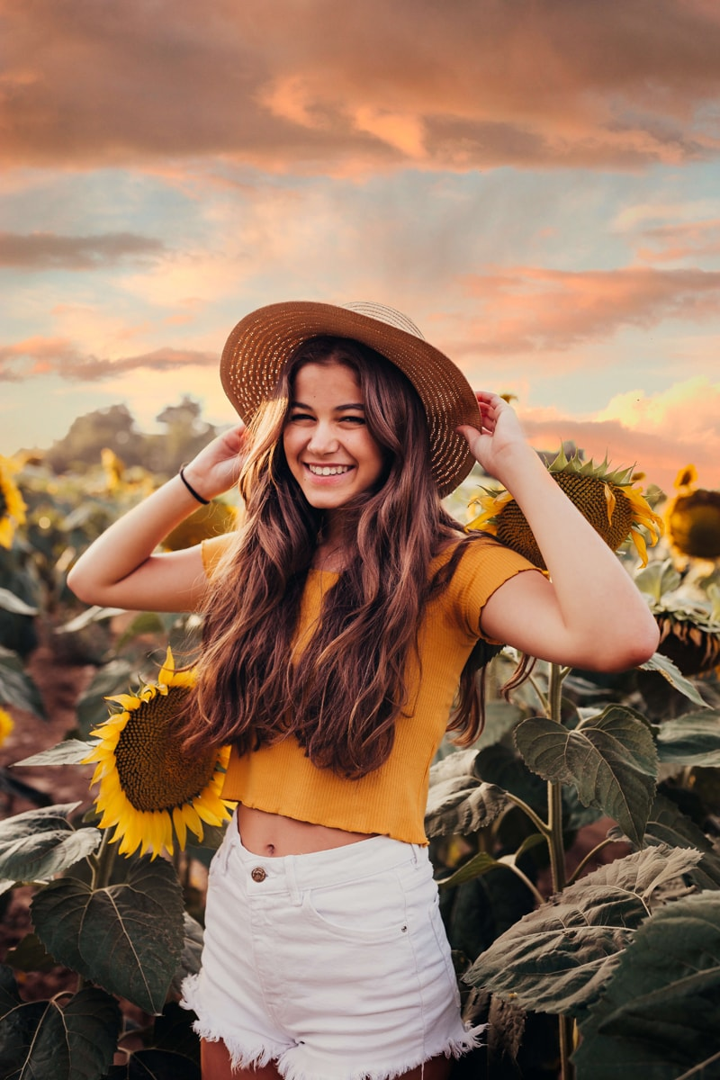 London Family Photographer, a young woman smiles outside, she stands in a field of sunflowers