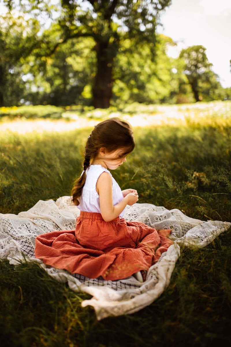 London Family Photographer, little girl sits on a blanket in a dreamy grassy field