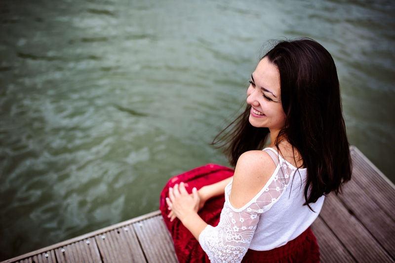 London Family Photographer, a young woman sits on the docks edge smiling, her feet in the water