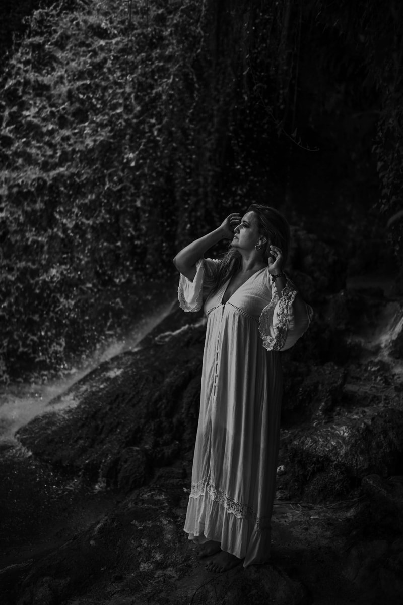 London Family Photographer, woman in white dress stands near a waterfall