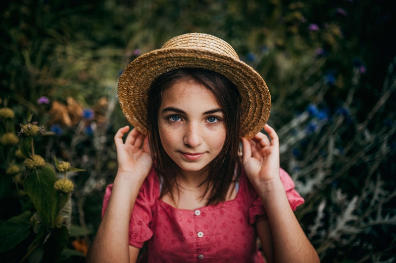 London Family Photographer, a young girl holds onto her straw hat as she stands in a field of flowers
