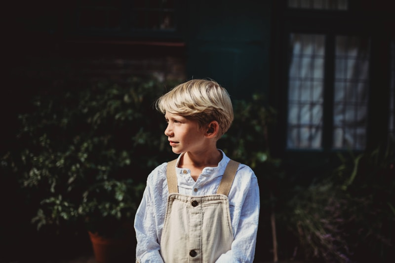 London Family Photographer, a boy stands outside a cottage covered in ivy, a pre-teen wearing overalls