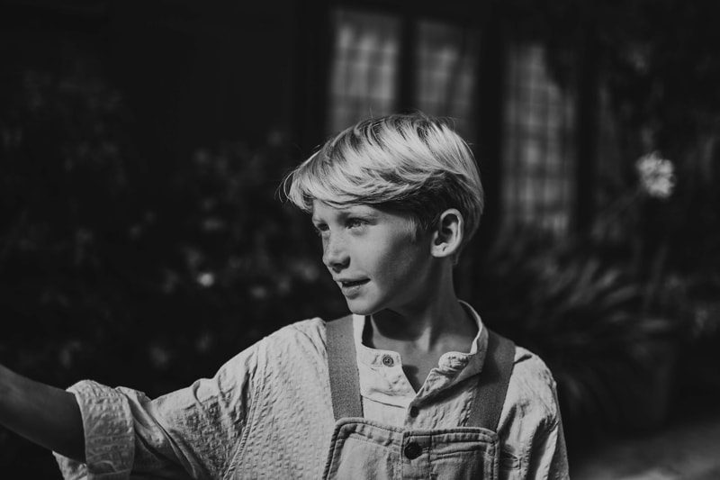 London Family Photographer, a young boy in overalls smiles outdoors