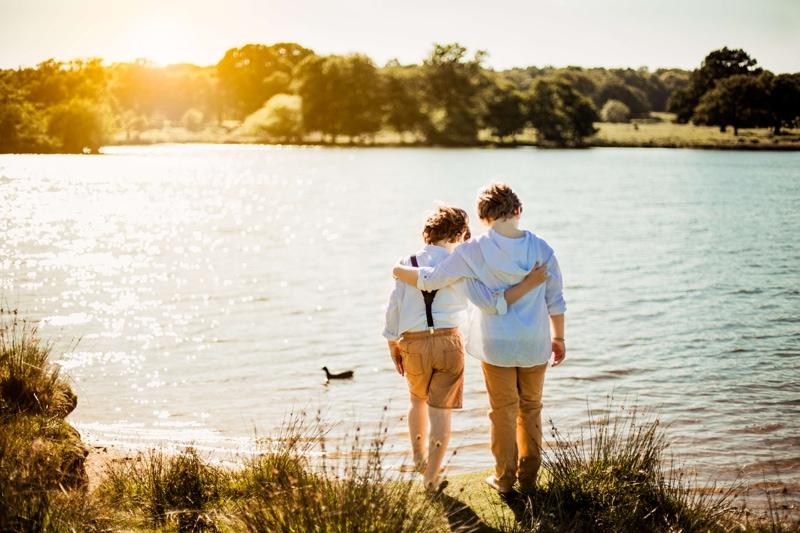 London Family Photographer, two young brothers stand arm in arm near a large lake at golden hour
