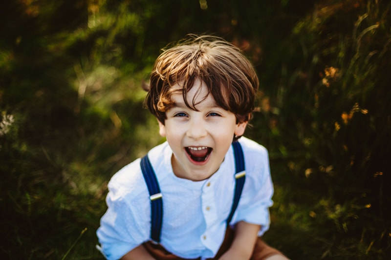 London Family Photographer, a young boy laughs and smiles as he sits in the grass outdoors