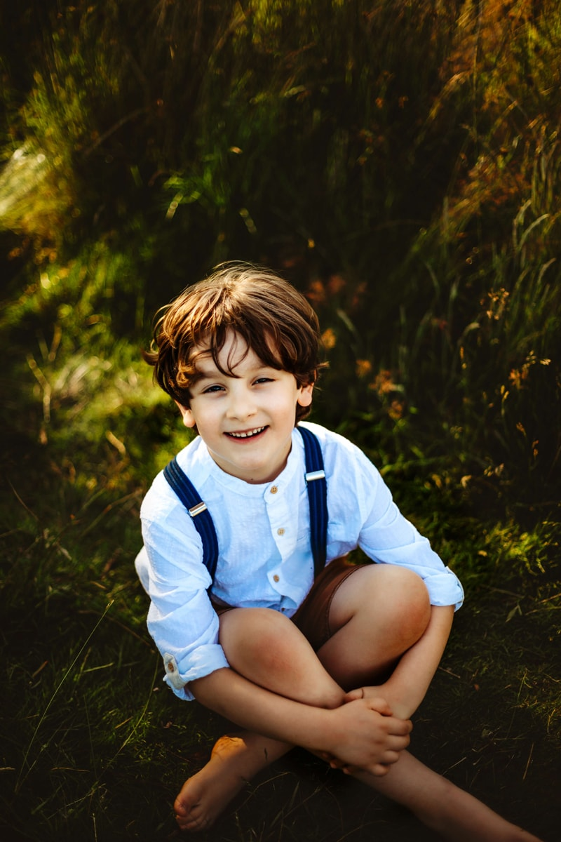 London Family Photographer, little boy sits in the grass cross-legged and happy