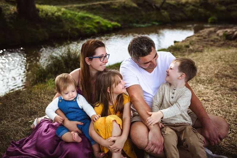 London Family Photographer, a young family of five sit next to a quiet stream