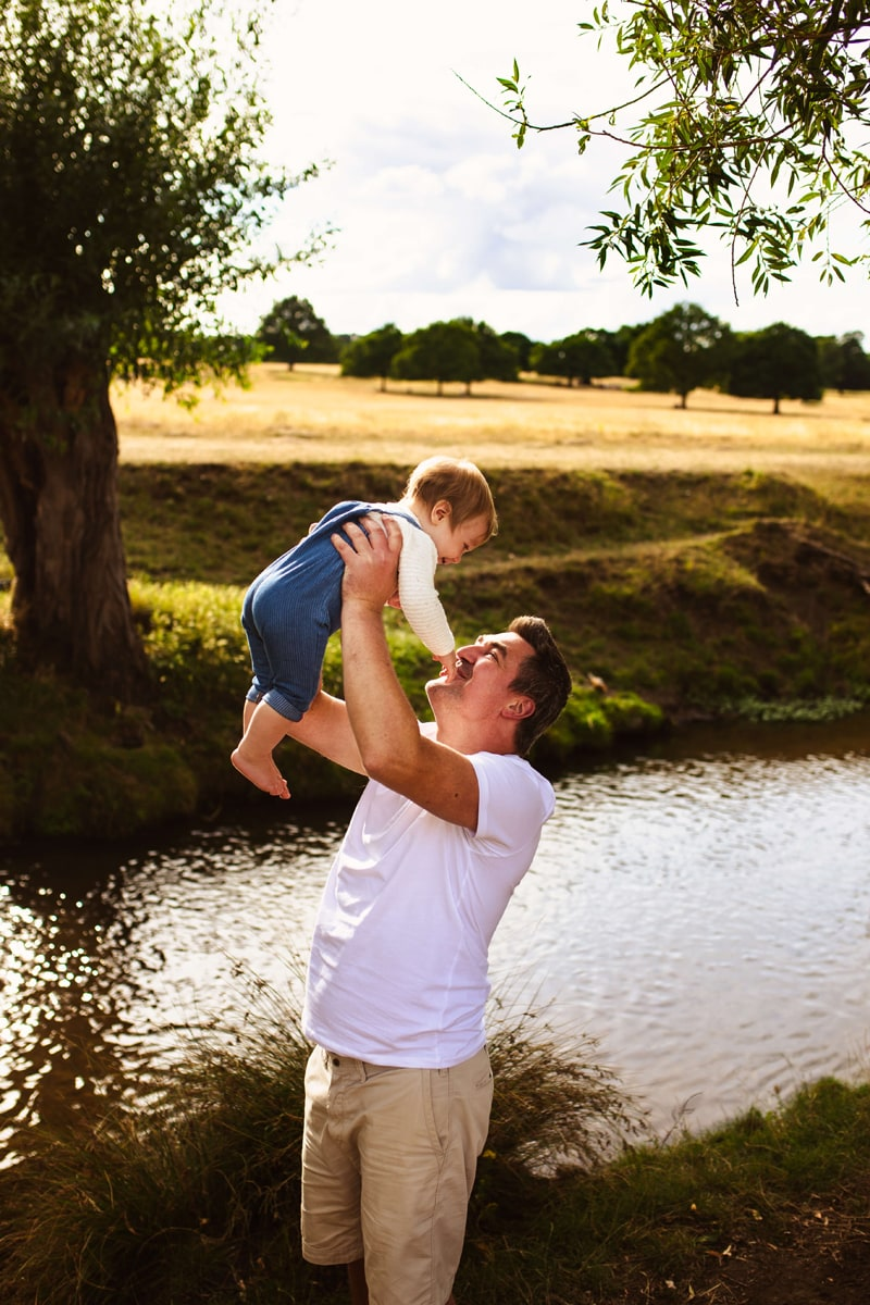 London Family Photographer, a father holds up his baby in the air near a stream outdoors