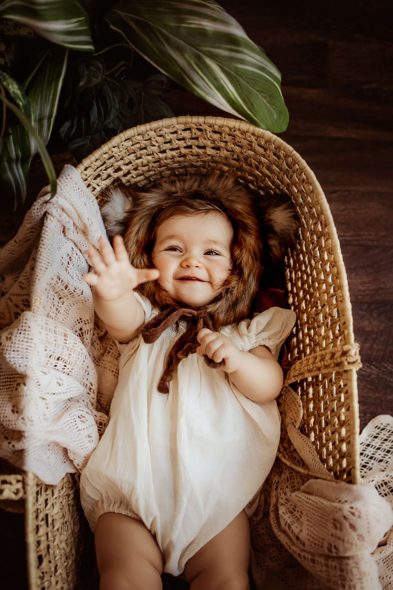 London Family Photographer, baby lays in a basket with a furry cap smiling