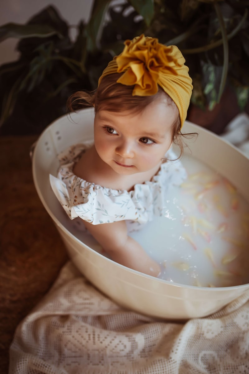 London Family Photographer, a baby girl sits in a small tub enjoying a milk bath, a big bow in her hair