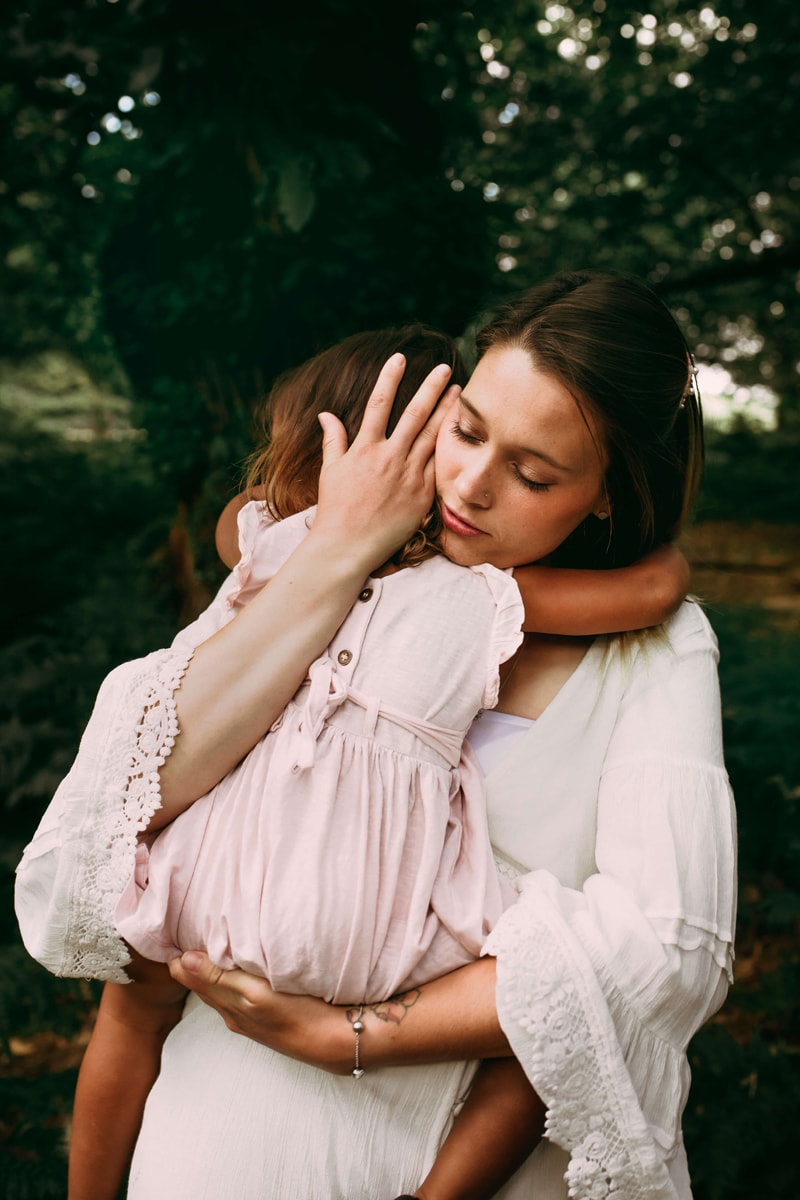 London Family Photographer, a young mother embraces her toddler daughter in the forest