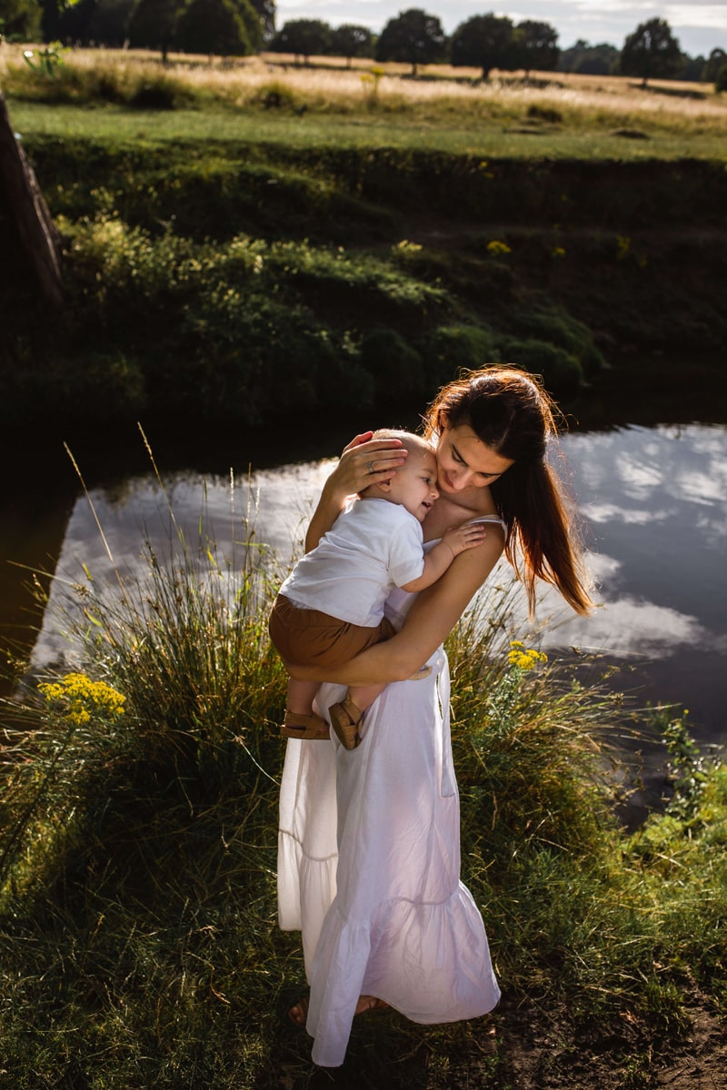 London Family Photographer, a woman holds her baby outdoors near fields of grass and streams