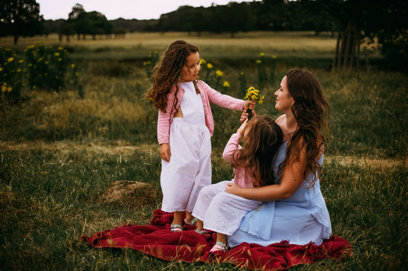 London Family Photographer, a mother sits on a blanket holding onto her daughter in a grassy field, another daughter brings her wildflowers,