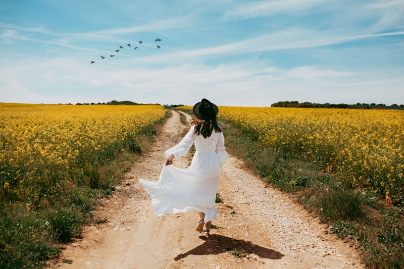 London Family Photographer, a woman in a white dress runs on a road through a flowery field, birds fly in pattern above her