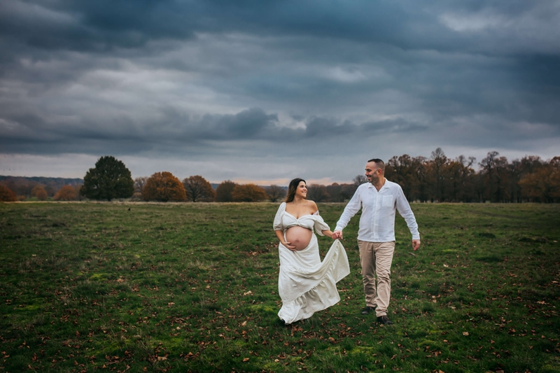 London Family Photographer, a man and expecting woman walk hand in hand through a grassy field