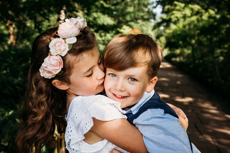 London Family Photographer, a little girl with a flower crowns hugs and kisses a smiling little boy