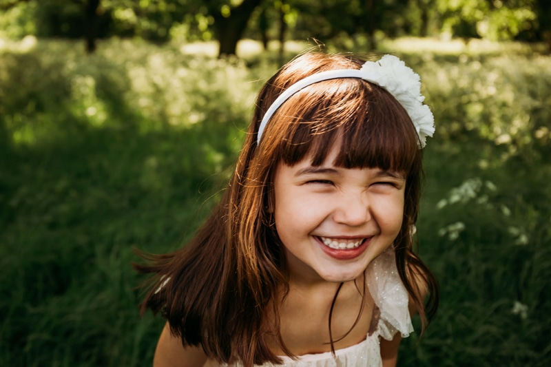 London Family Photographer, a young girl grins smiling as she has fun outside