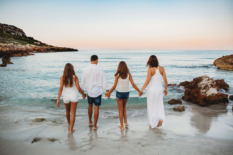 London Family Photographer, a family of four with two daughters walk toward the ocean holding hands