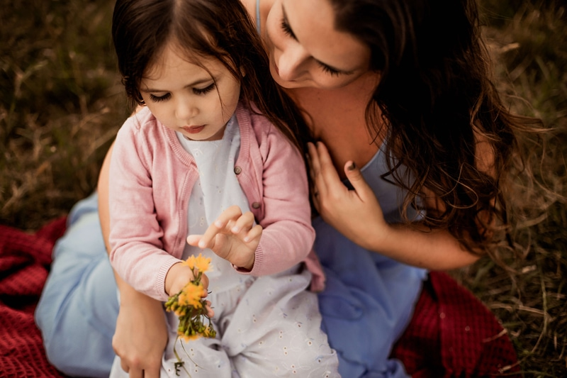 London Family Photographer, a mother and her young daughter sit on a blanket in the grass, the daughter holds wildflowers