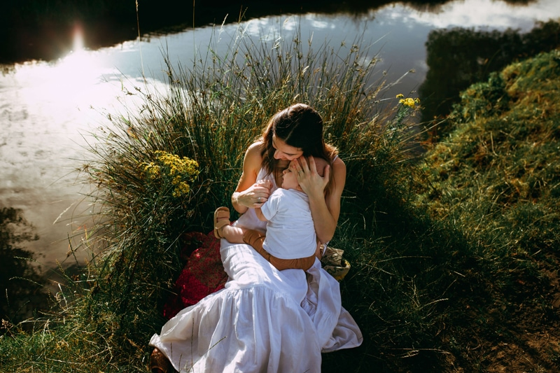 London Family Photographer, Mother embraces her baby while sitting near a lakeshore