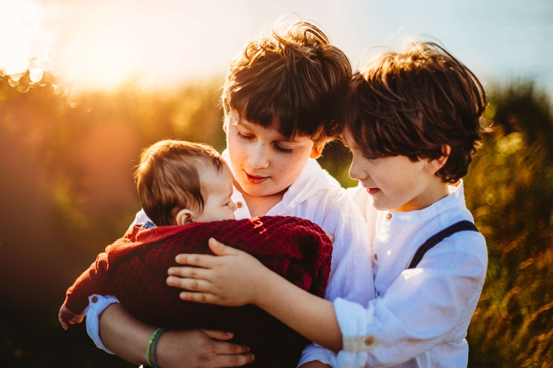 London Family Photographer, two young boys hold onto their new baby sibling, they are older brothers